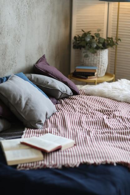 Cama com travesseiros e livro aberto Foto gratuita