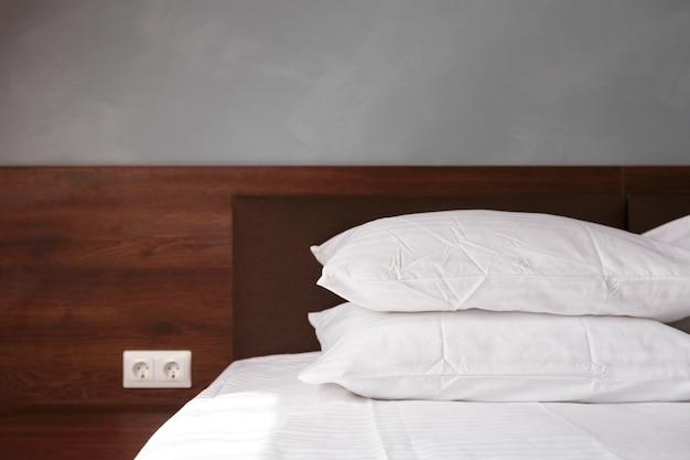 Cama de empregada com almofadas brancas limpas e lençóis na sala de beleza. Foto Premium