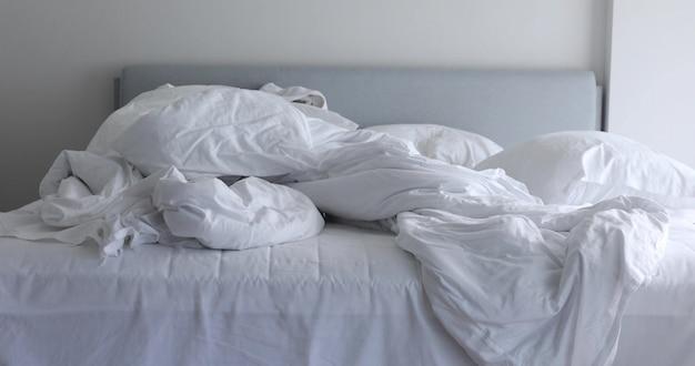 Cama desfeita branca com cobertor desarrumado amassado e travesseiro na luz da manhã Foto Premium