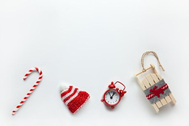 Cama plana de natal, gorro de inverno, bengala de doces, pequeno relógio analógico vermelho, trenó no fundo branco, Foto Premium
