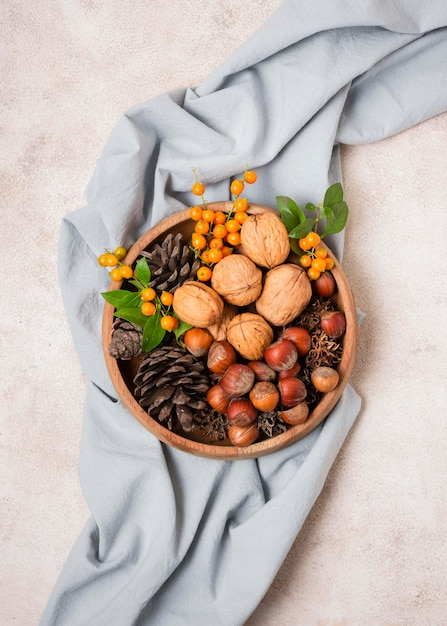 Camada plana da tigela outonal com pinhas e tecido Foto gratuita