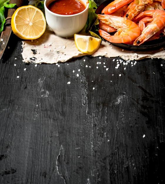 Camarão com molho de tomate no tecido velho. no quadro negro. Foto Premium