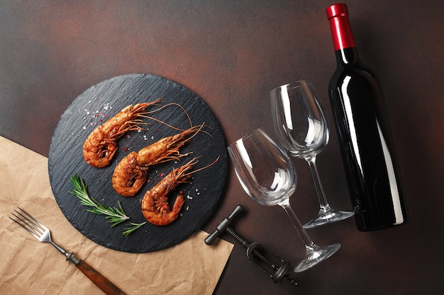 Camarão com uma garrafa de vinho. vista do topo. espaço livre para o seu texto. no antigo fundo Foto Premium
