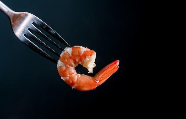 Camarão cozido no vapor na forquilha isolada no fundo escuro com espaço da cópia. buffet de frutos do mar no conceito de restaurante. use para promoções de buffet de frutos do mar Foto Premium