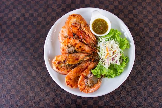 Camarão grelhado com frutos do mar decorados com vegetais e molho picante quente em prato de cerâmica branca Foto Premium
