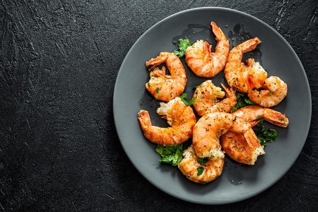 Camarão grelhado no prato no escuro Foto Premium