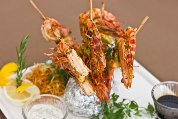 Camarões cozidos em espetos de madeira. servir com molhos e ervas em um prato branco. Foto Premium