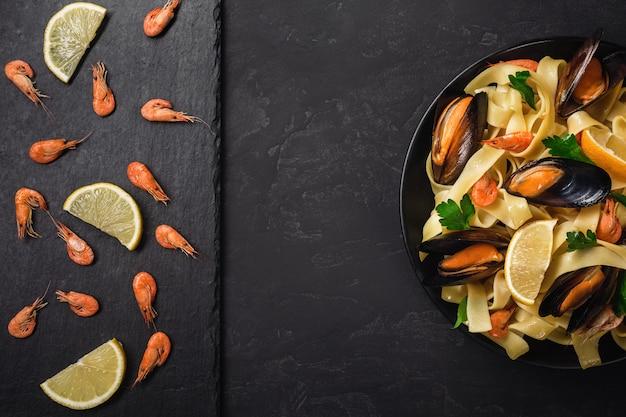 Camarões crus frescos ou camarões vermelhos fervidos com especiarias e limão na pedra da ardósia no fundo de pedra escuro. marisco, vista superior, configuração plana, espaço de cópia. Foto Premium