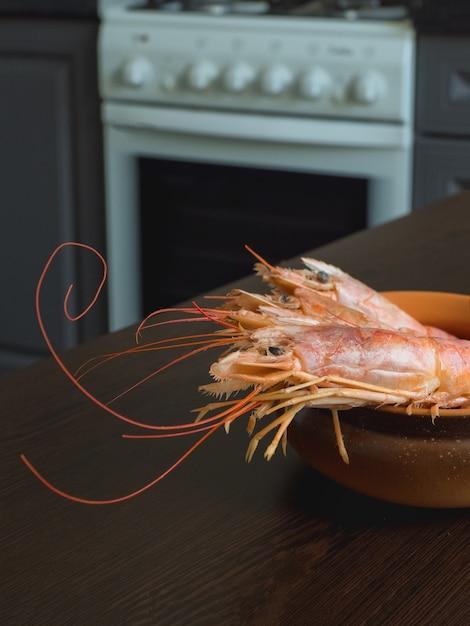 Camarões frescos na mesa da cozinha em uma tigela. Foto Premium