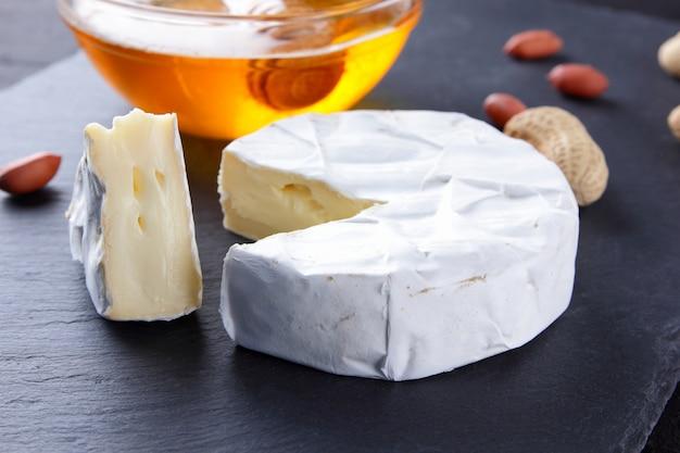 Camembert e mel na placa de ardósia preta. queijo com mofo e amendoim. queijo e nozes na placa de pedra Foto Premium