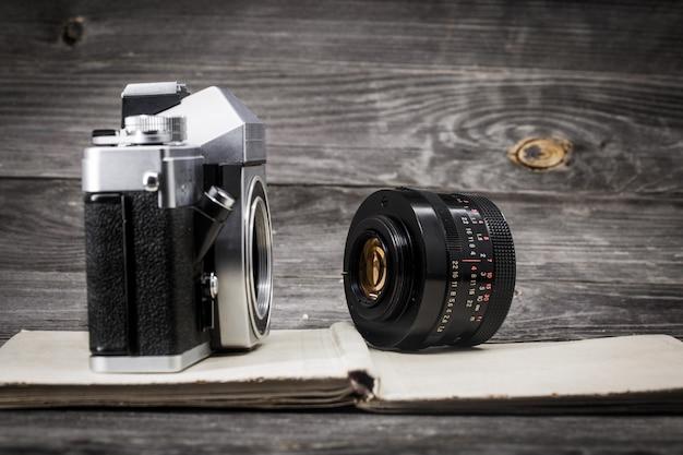 Câmera antiga no livro vintage, fundo de madeira Foto Premium