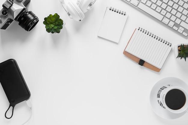 Câmera; banco de poder; cacto vegetal; diário; xícara de chá e teclado na mesa branca Foto gratuita