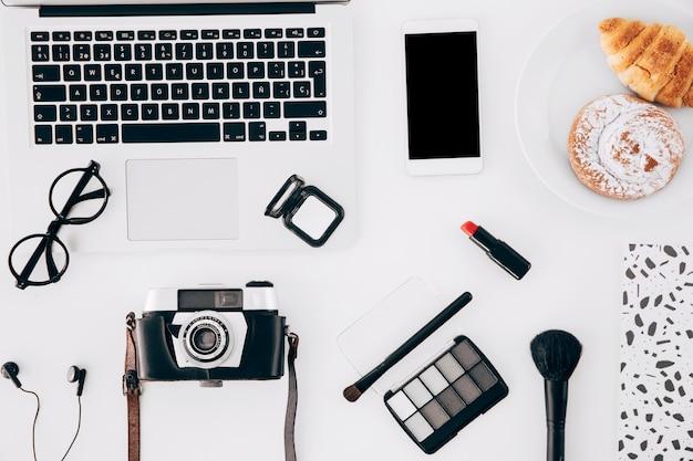 Câmera; computador portátil; celular; produto de cosméticos e pastelaria assada na mesa branca Foto gratuita