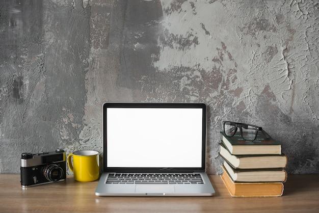Câmera; copo; livros empilhados; óculos e laptop com tela branca em branco na mesa de madeira Foto gratuita