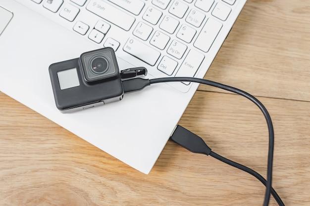 Câmera de ação conectada a um laptop branco Foto Premium