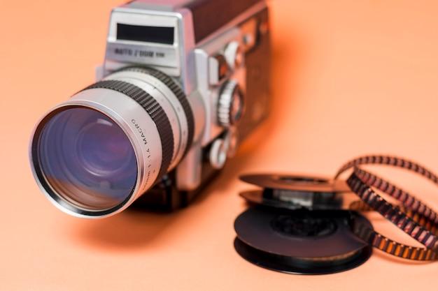 Câmera de filmadora vintage com tira de filme em fundo colorido pêssego Foto gratuita