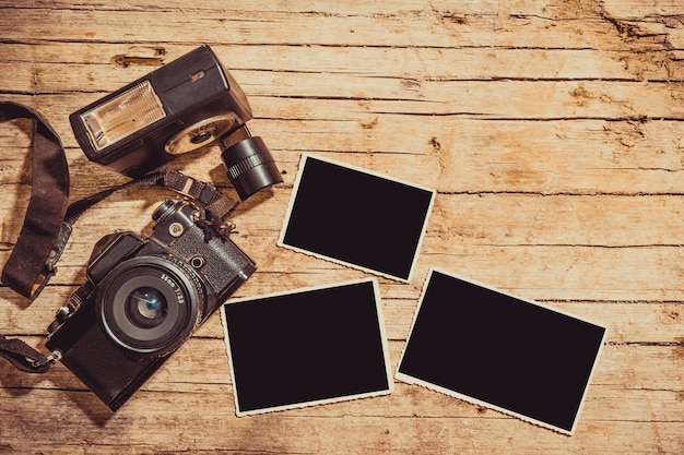 Câmera de filme vintage e duas molduras em branco na mesa de madeira Foto Premium