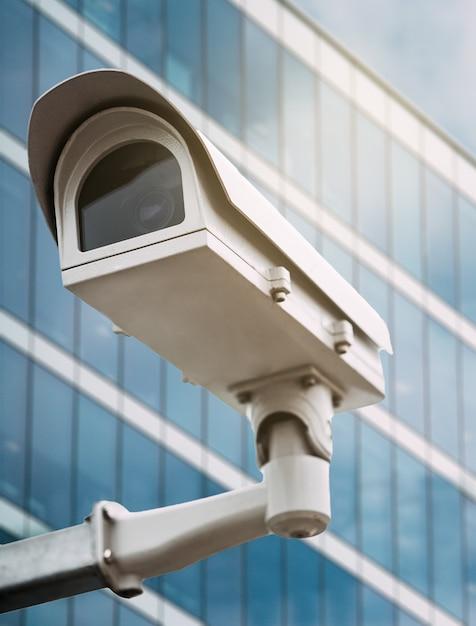 Câmera de segurança com um edifício de vidro no fundo Foto Premium