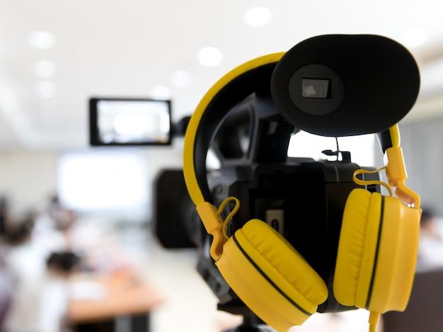 Câmera de vídeo em participantes de gravação de sala de conferências de negócios e fone de ouvido Foto Premium