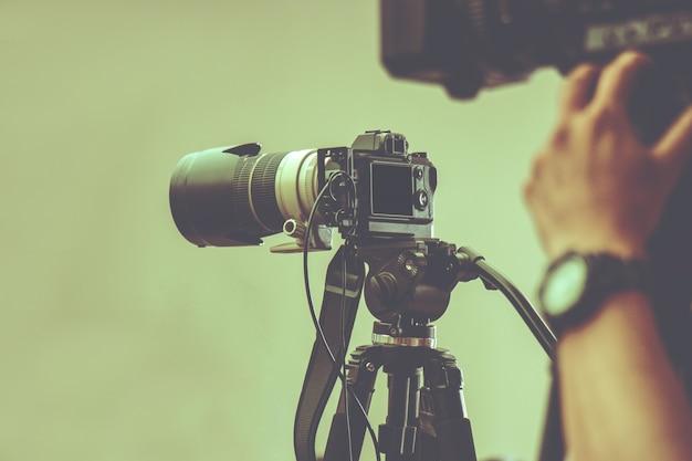Câmera de vídeo profissional com tripé em espera para fotografar na produção de estúdio Foto Premium