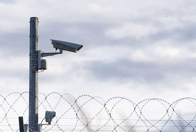 Câmera de vigilância e arame farpado Foto Premium