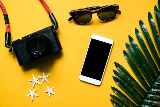 Câmera de vista op, smartphone, óculos de sol, estrela do mar e folha de palmeira em amarelo Foto Premium