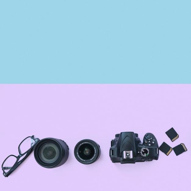 Câmera digital profissional com acessórios e espetáculo em fundo duplo Foto gratuita