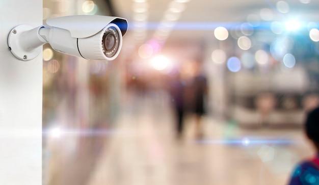 Câmera do cctv em um branco da parede. segurança com fundo desfocado supermercado Foto Premium