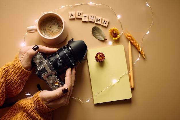 Câmera fotográfica, café e suéter de malha laranja Foto Premium