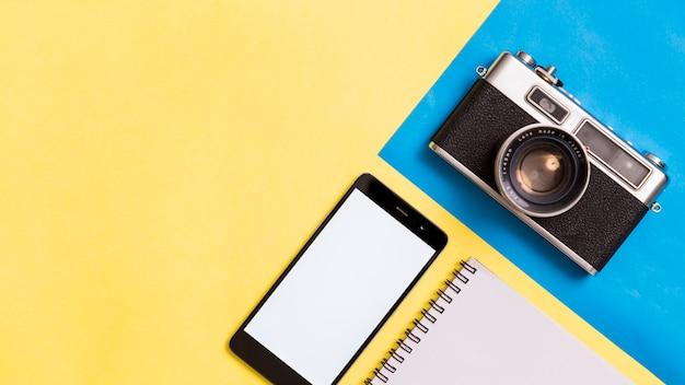 Câmera fotográfica vintage e smartphone em fundo colorido Foto Premium