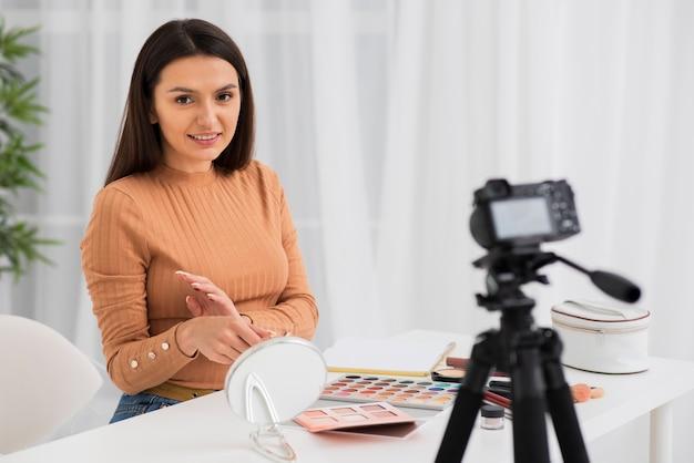 Câmera gravação mulher enquanto tenta maquiagem Foto Premium