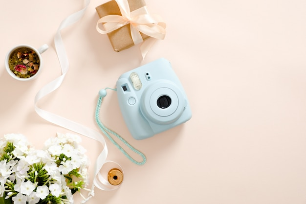 Câmera instantânea moderna, margarida flores, xícara de chá, caixa de presente, fita em fundo rosa pastel Foto Premium