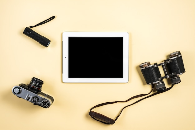 Câmera; lanterna; tablet binocular e digital sobre fundo bege Foto gratuita