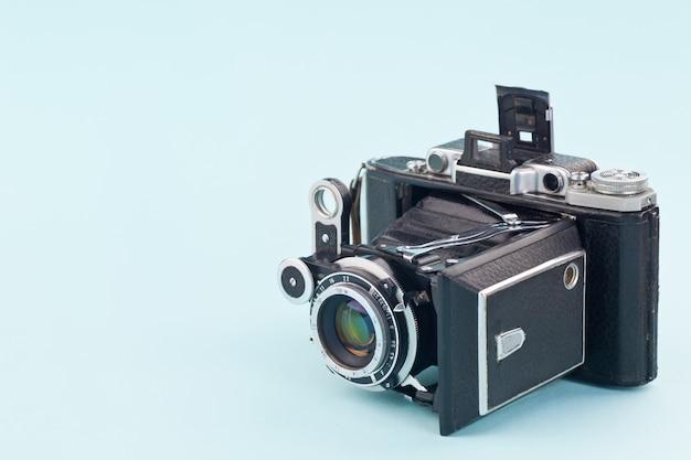 Câmera muito antiga em um fundo azul suave. Foto Premium