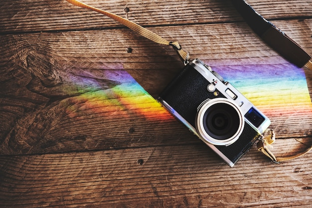 Câmera na mesa de madeira com reflexão de luzes de prisma Foto gratuita