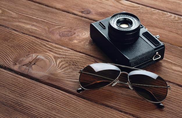 Câmera, óculos de sol. acessórios de estrada em uma mesa de madeira. Foto Premium