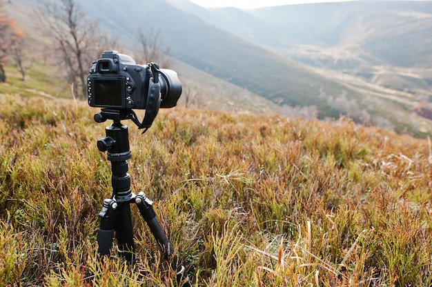 Câmera profissional moderna do dslr em um tripé, fotografia ao ar livre na vida selvagem. fundo de montanhas. Foto Premium