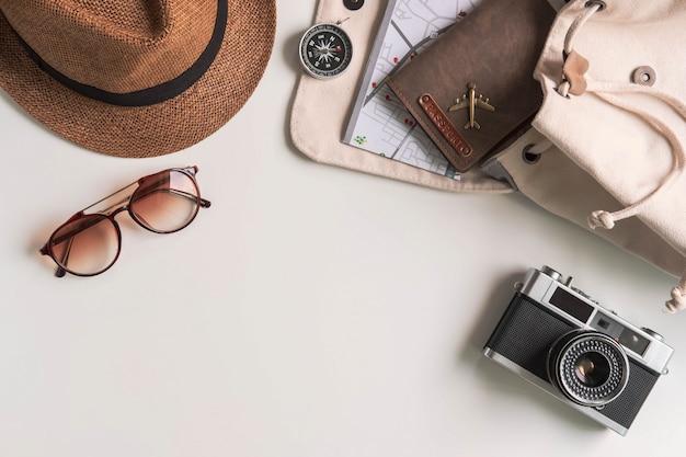 Câmera retro com acessórios de viagem e itens em fundo branco, com espaço de cópia, conceito de viagens Foto Premium