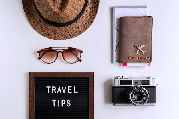 Câmera retro com avião de brinquedo, mapa e passaporte em fundo branco, conceito de dicas de viagem Foto Premium