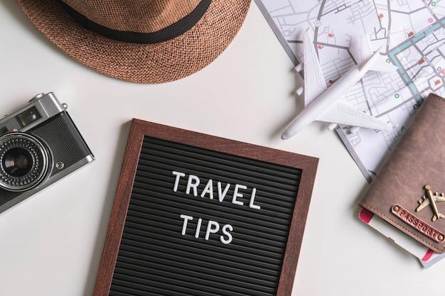 Câmera retro com avião de brinquedo, mapa e passaporte em fundo branco Foto Premium