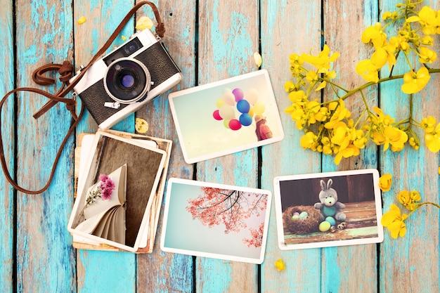 Câmera retro e álbum de fotos de papel na mesa de madeira com flores Foto Premium