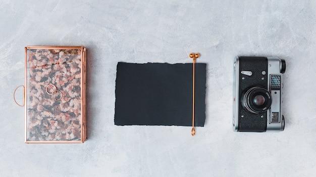 Câmera retro perto de papel escuro e caixa criativa Foto gratuita