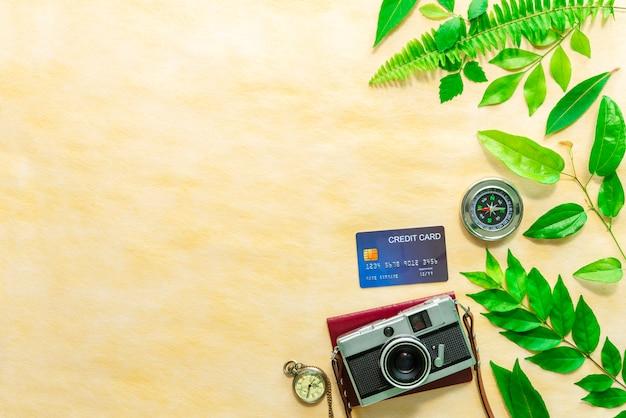 Câmera vintage, cartão de crédito, passaporte, relógio de bolso e bússola na mesa Foto Premium
