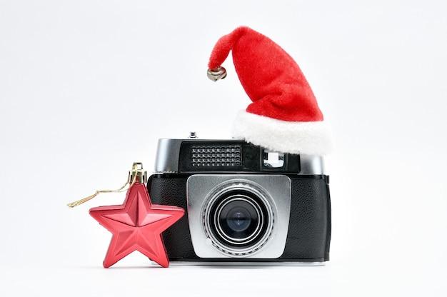 Câmera vintage cercada por uma árvore de natal e brinquedos em um espaço em branco isolado Foto Premium