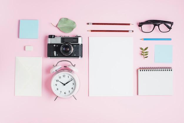 Câmera vintage; despertador e artigos de papelaria no fundo rosa Foto gratuita