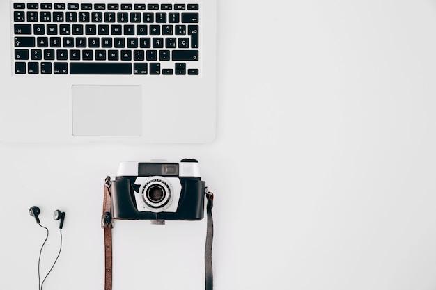 Câmera vintage; fone de ouvido e um laptop aberto no fundo branco Foto gratuita