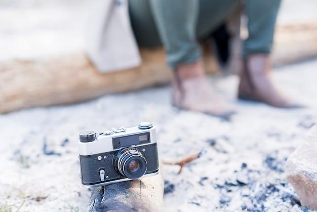 Câmera vintage no log com o viajante no fundo Foto gratuita