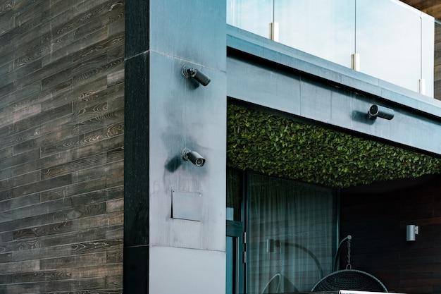 Câmeras de vigilância pretas instaladas na face de um prédio preto com lindas varandas. jardim no teto. ripas horizontais de madeira. projeto arquitetônico. câmera de cftv. privacidade. segurança. espião Foto Premium