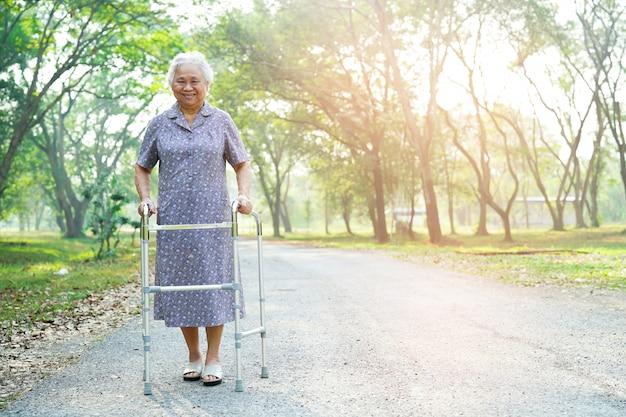 Caminhada paciente asiática ou idosa asiática da senhora idosa com o caminhante no parque. Foto Premium
