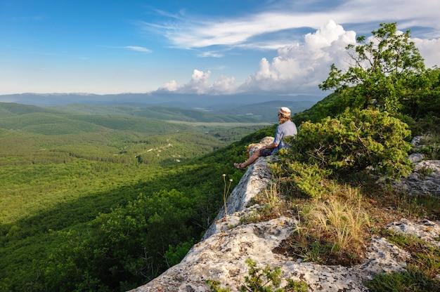 Caminhadas homem em raios de sol sentado na borda Foto Premium